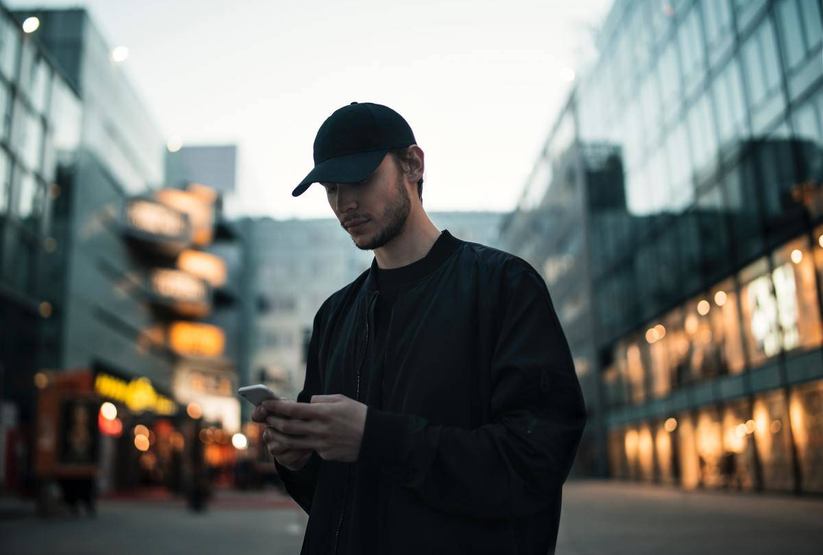 man in black hat and sweatshirt texting by building