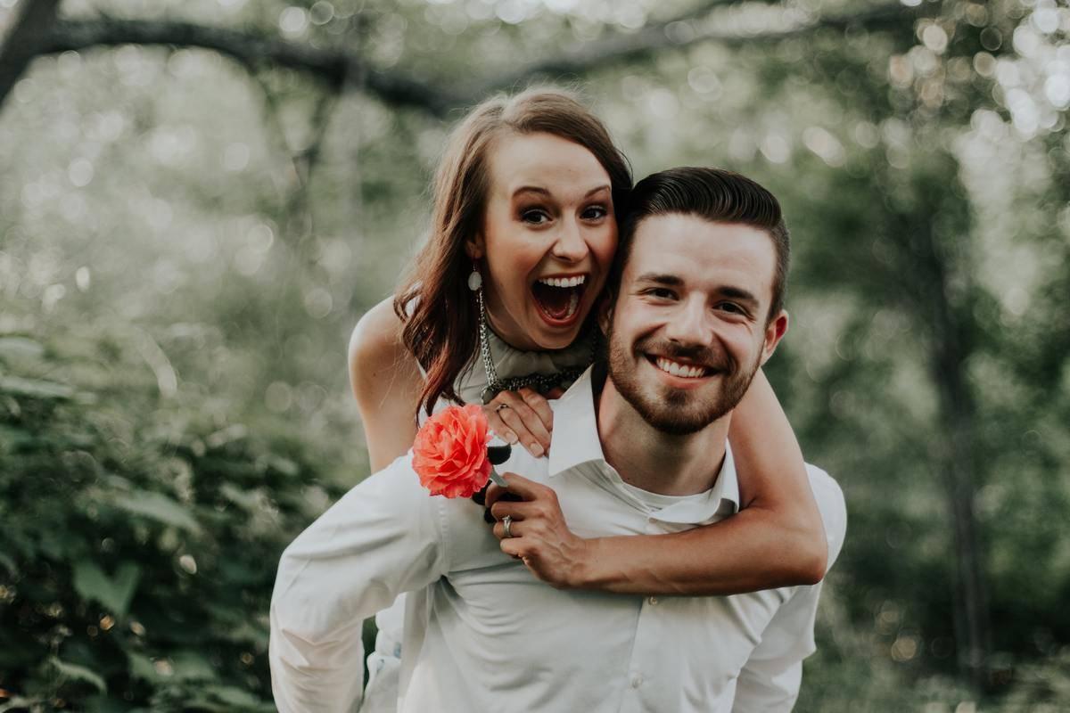 man piggybacks smiling woman holding flower