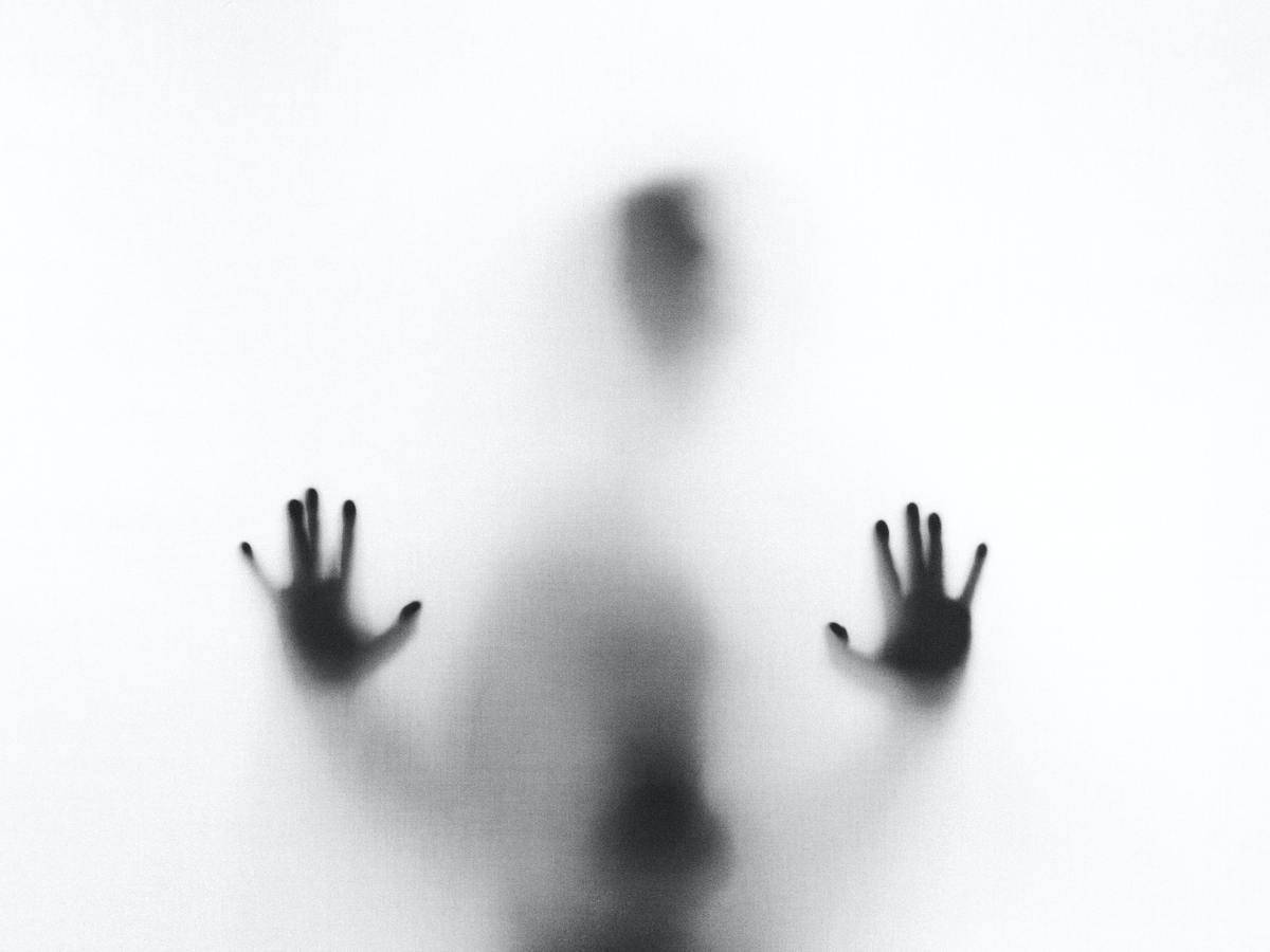 man puts hands on window like a shadow