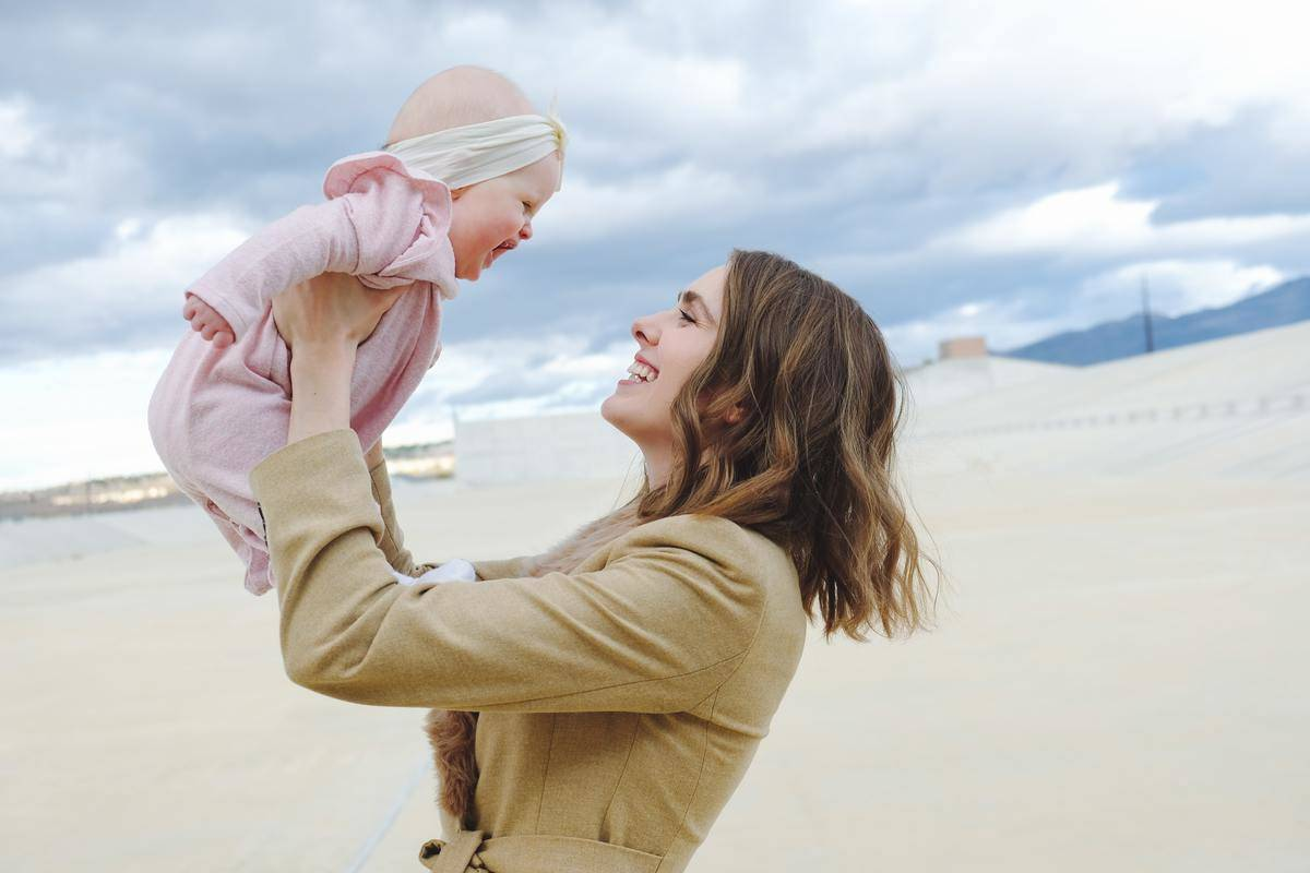 mom holds up baby at the beach