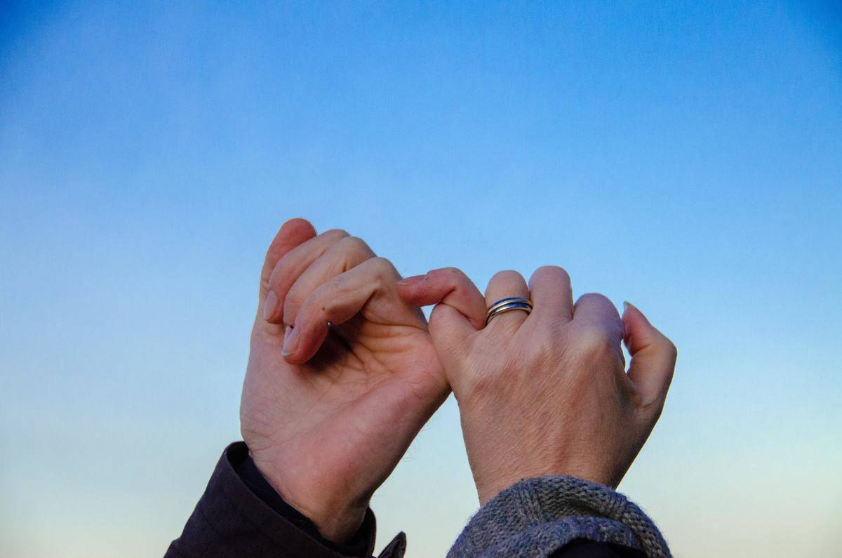 two hands pinky promise in the sky