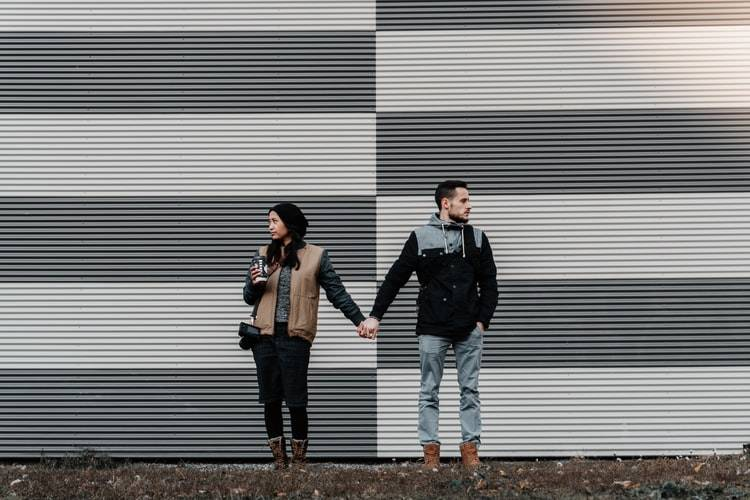 Couple holding hands but looking away from one another