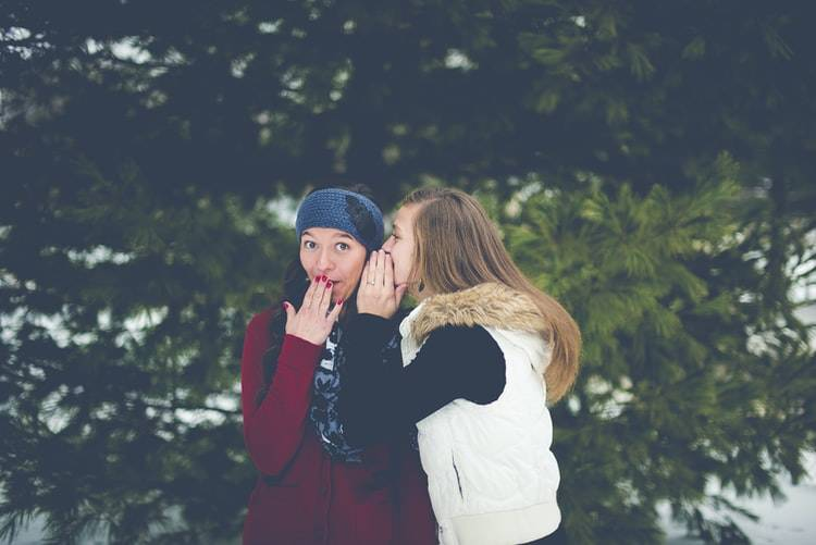 woman whispering something to another woman who has her hand over her mouth in shock