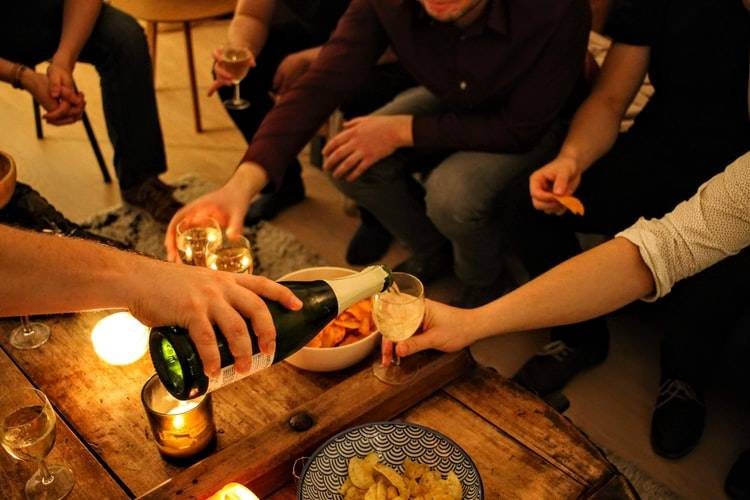 friends sitting around a table with snacks and drinks