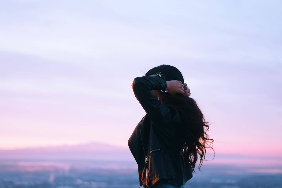 woman at sunset holding her hair
