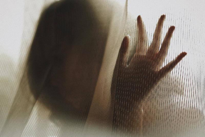 woman behind a curtain putting her hand up