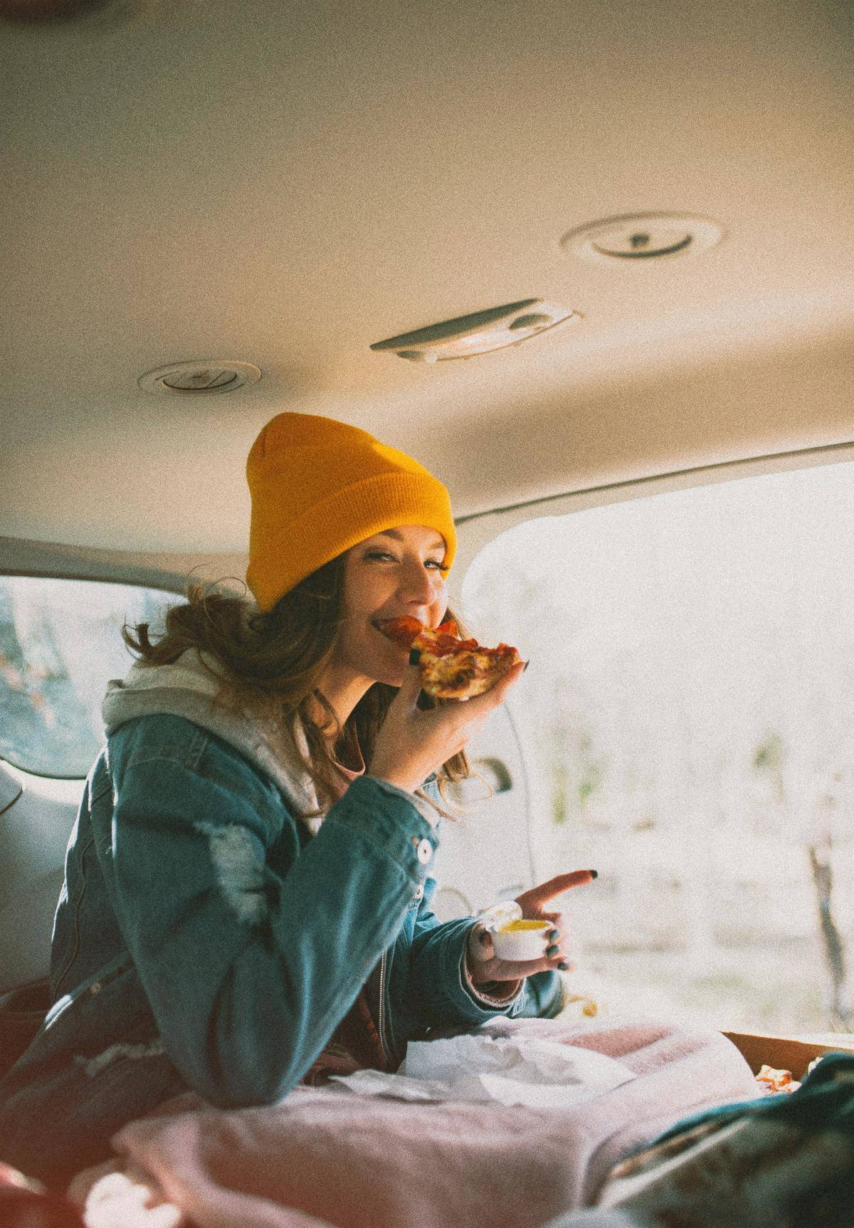woman eating pizza in a car