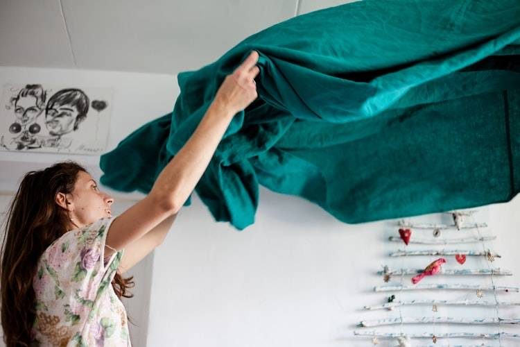 woman fluffing out and unwrinkling bedsheets