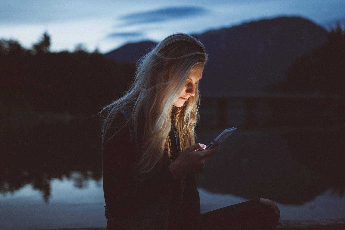 woman looking at her phone by the lake