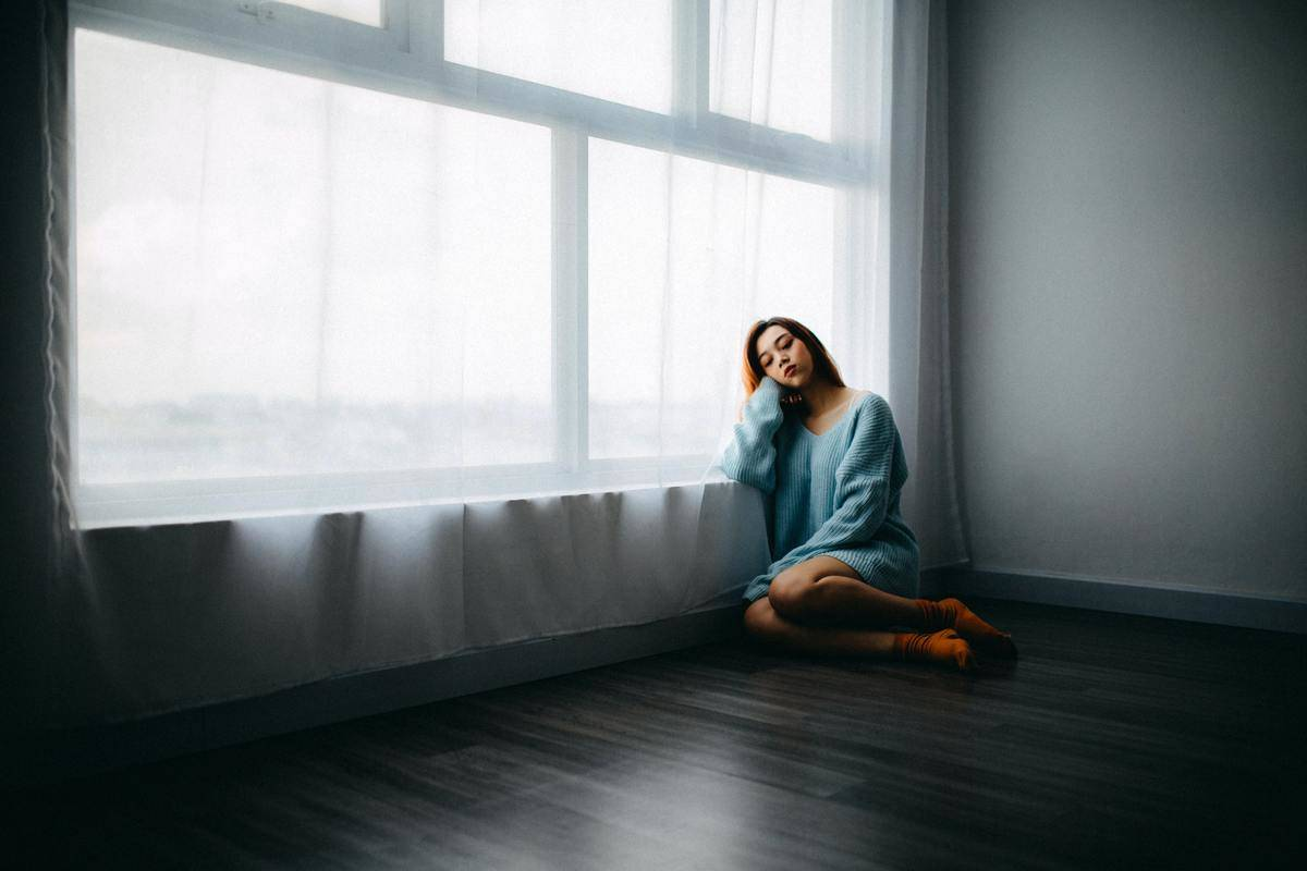 woman in blue sweater sitting against a window