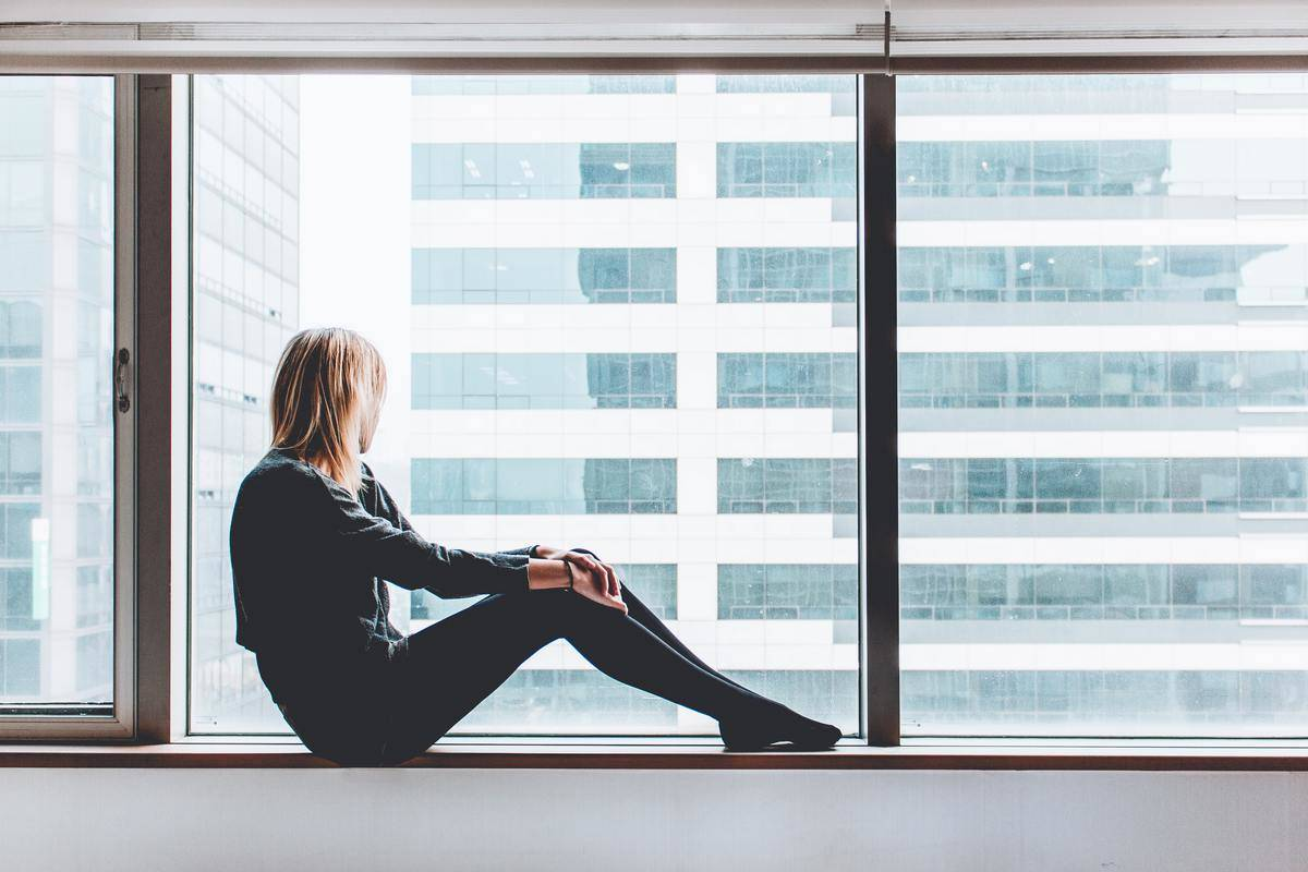 woman sitting by window facing building