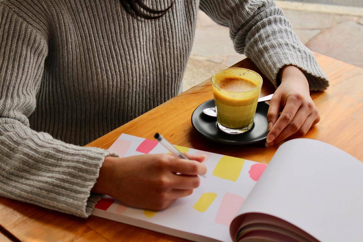woman taking notes with latte