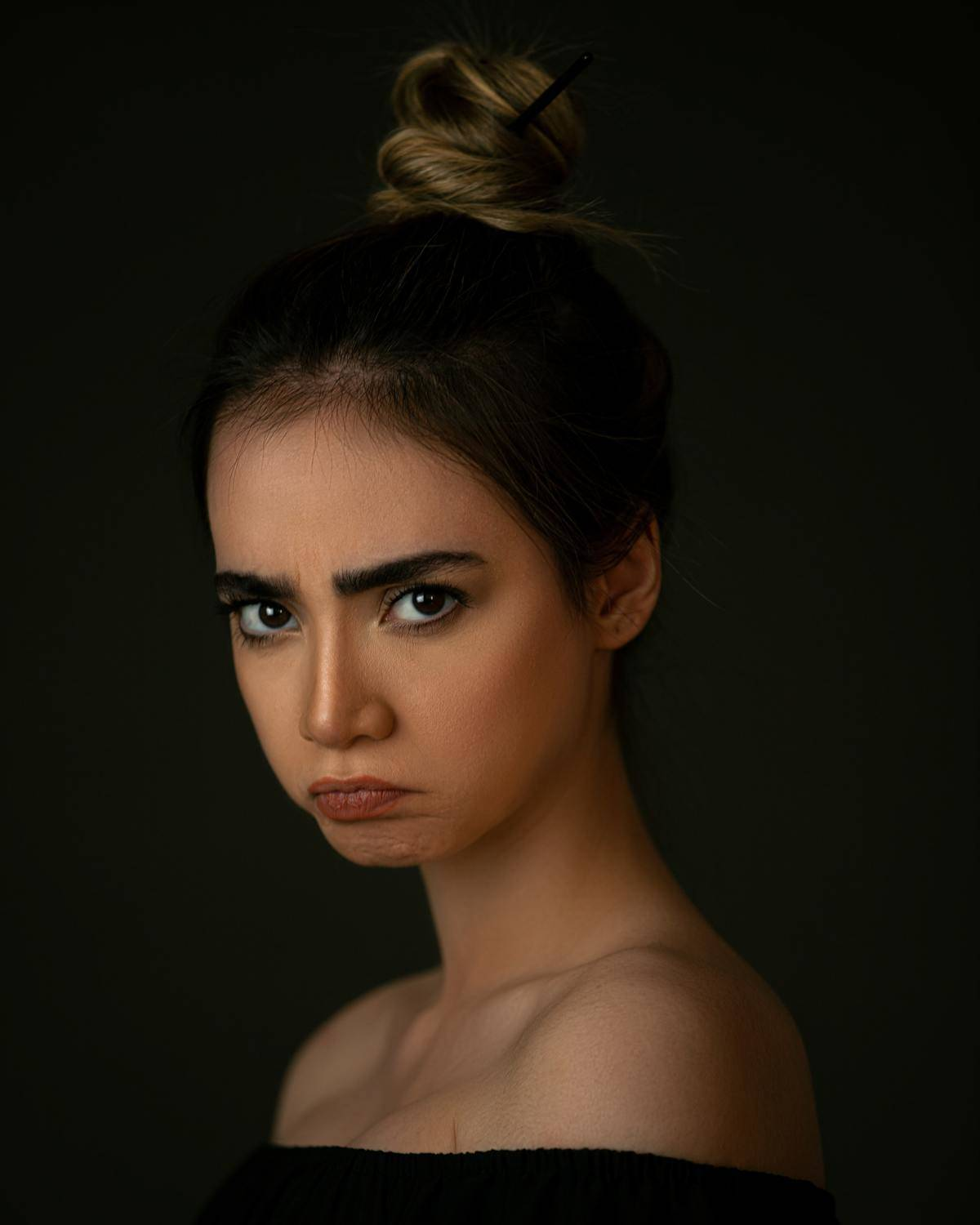 woman with pouty face and hair bun