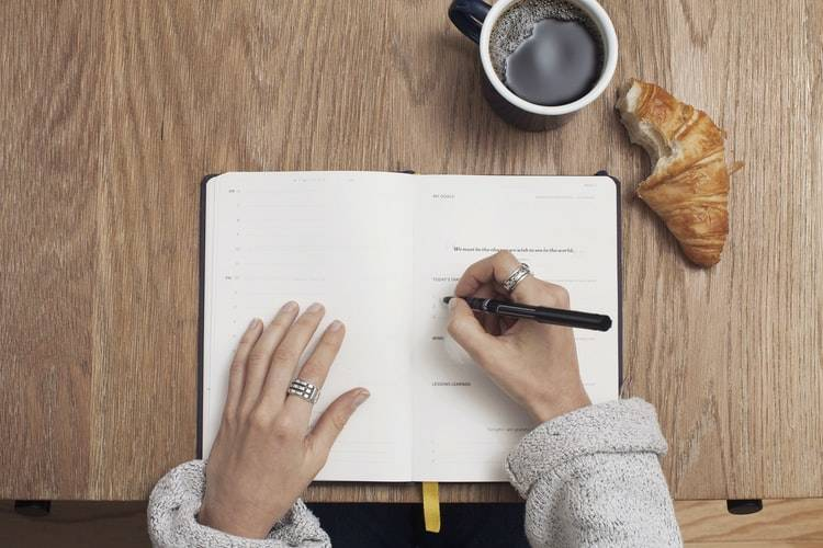 person writing a list with their breakfast beside them