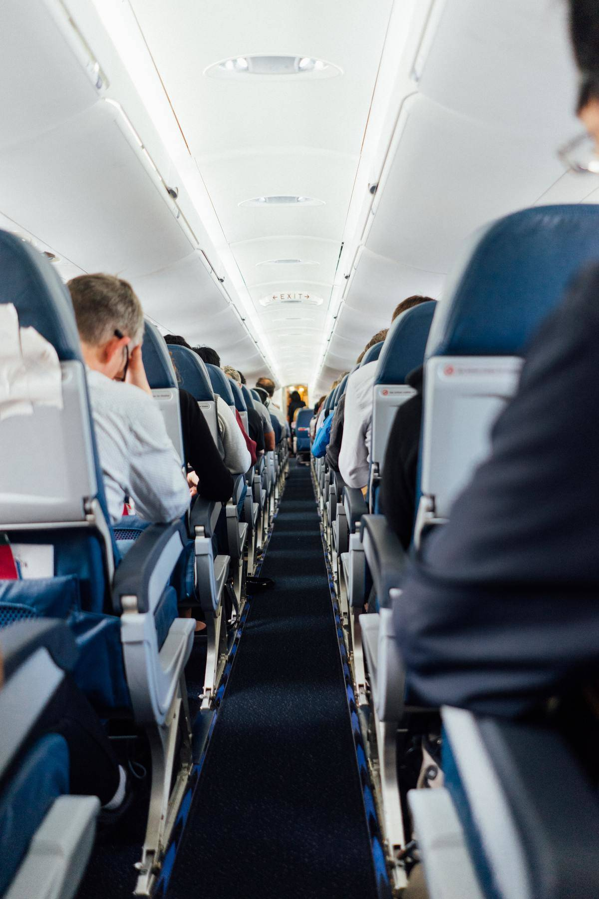 Aisle-view of people sitting inside a plane