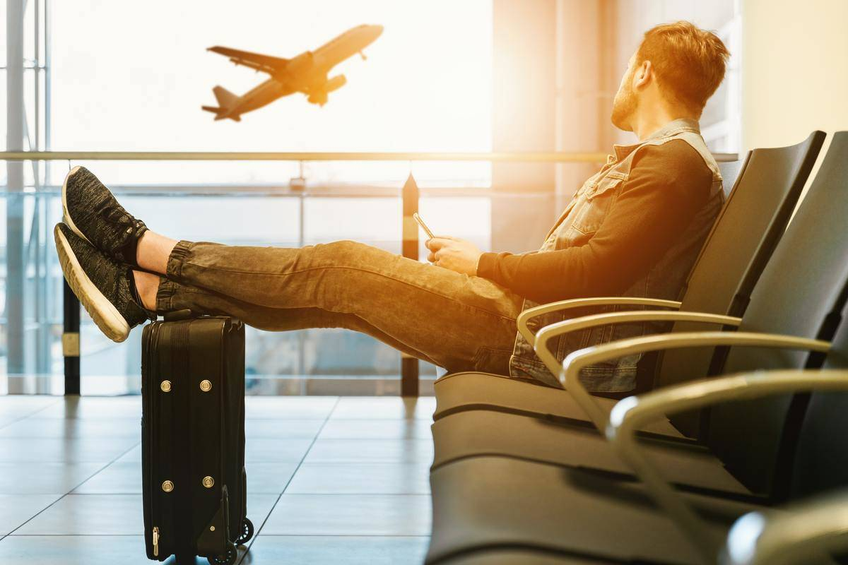 Man sitting in airport terminal and watching a plane take off
