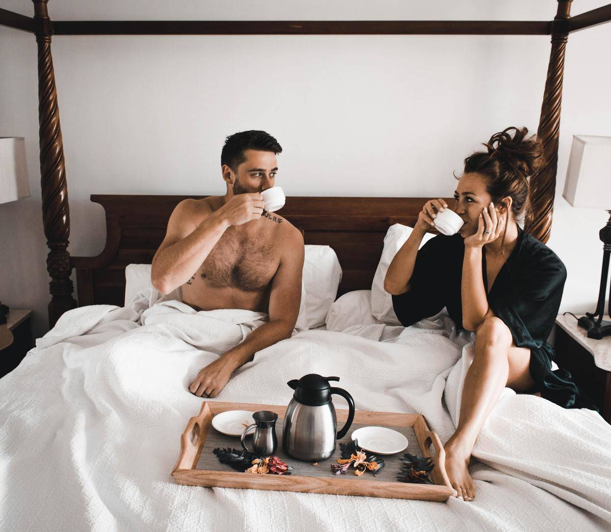 Couple drink coffee in bed; man is shirtless, woman in black robe