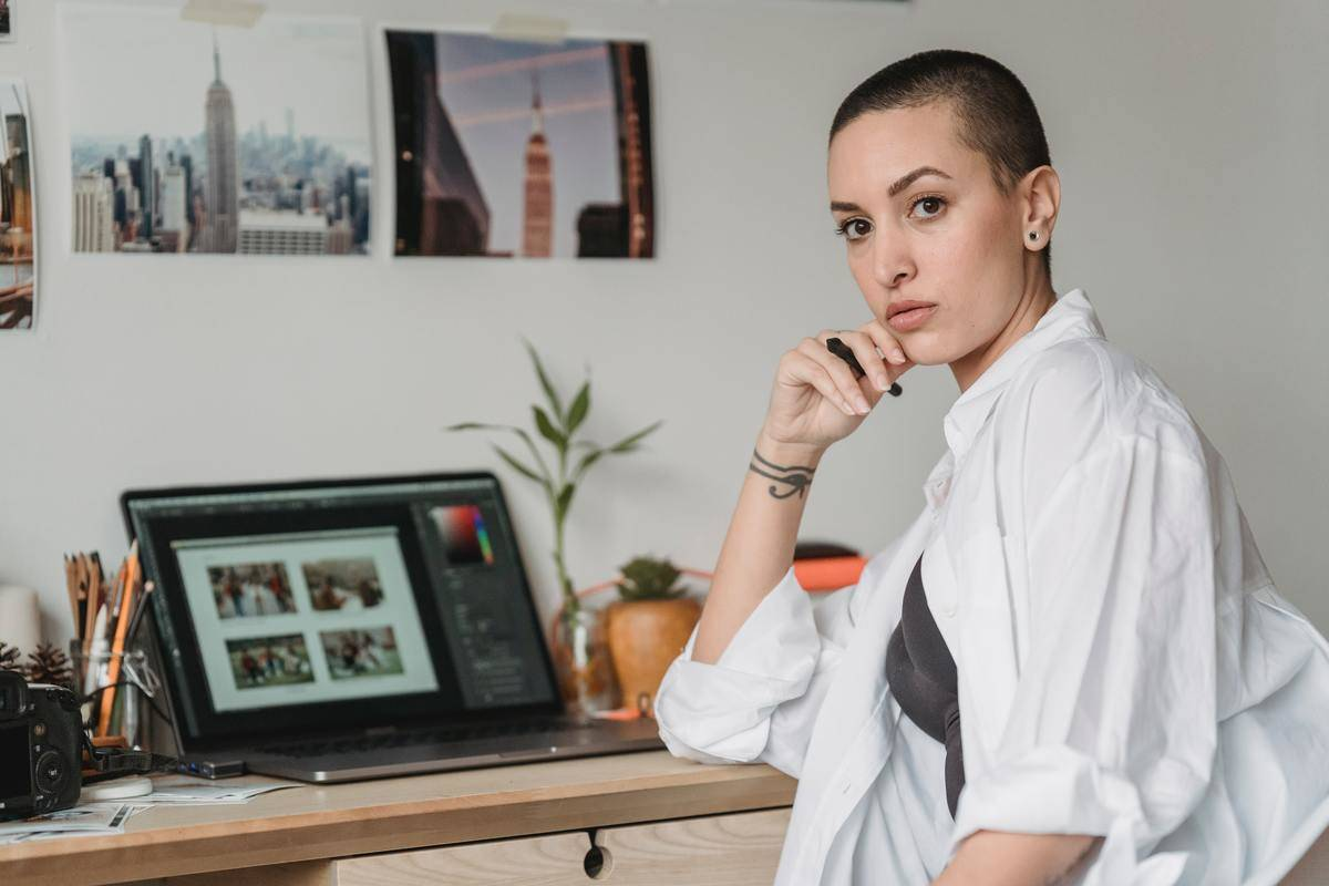 Woman sitting at desk with laptop open in front of her, she looks seriously at camera