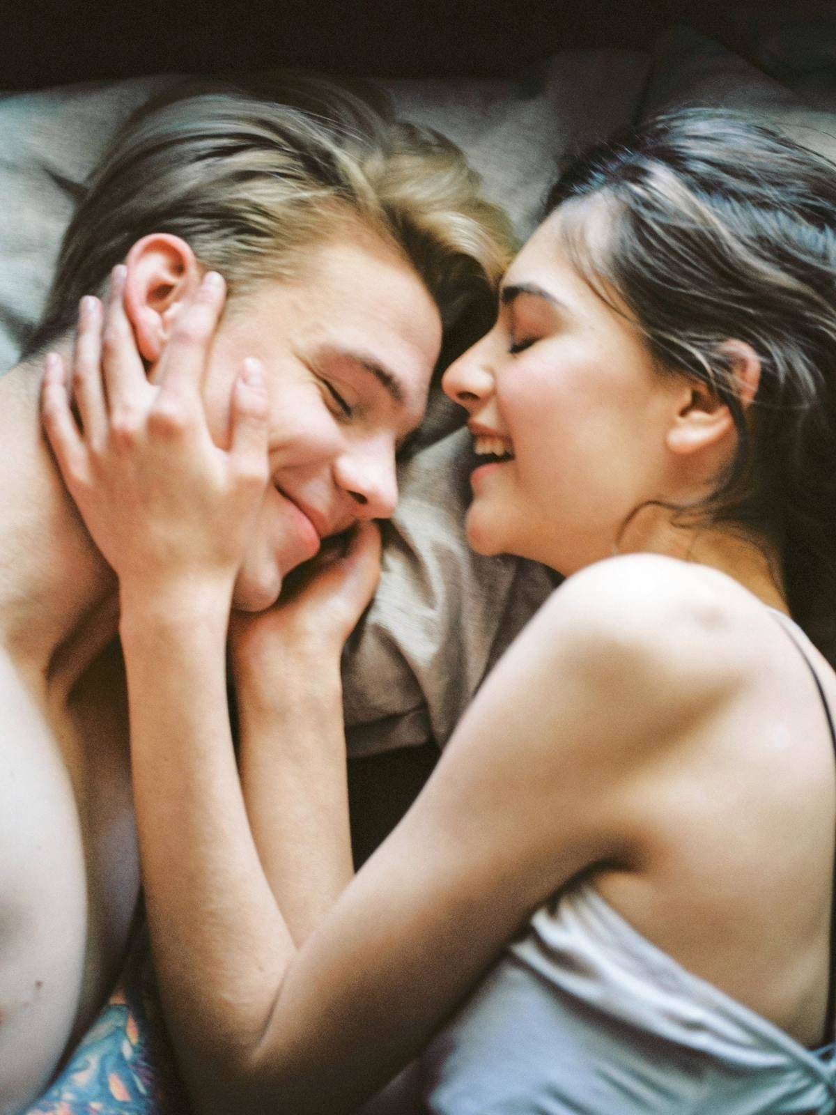 Young couple lying in bed, cuddling and smiling as the woman caresses the man's face