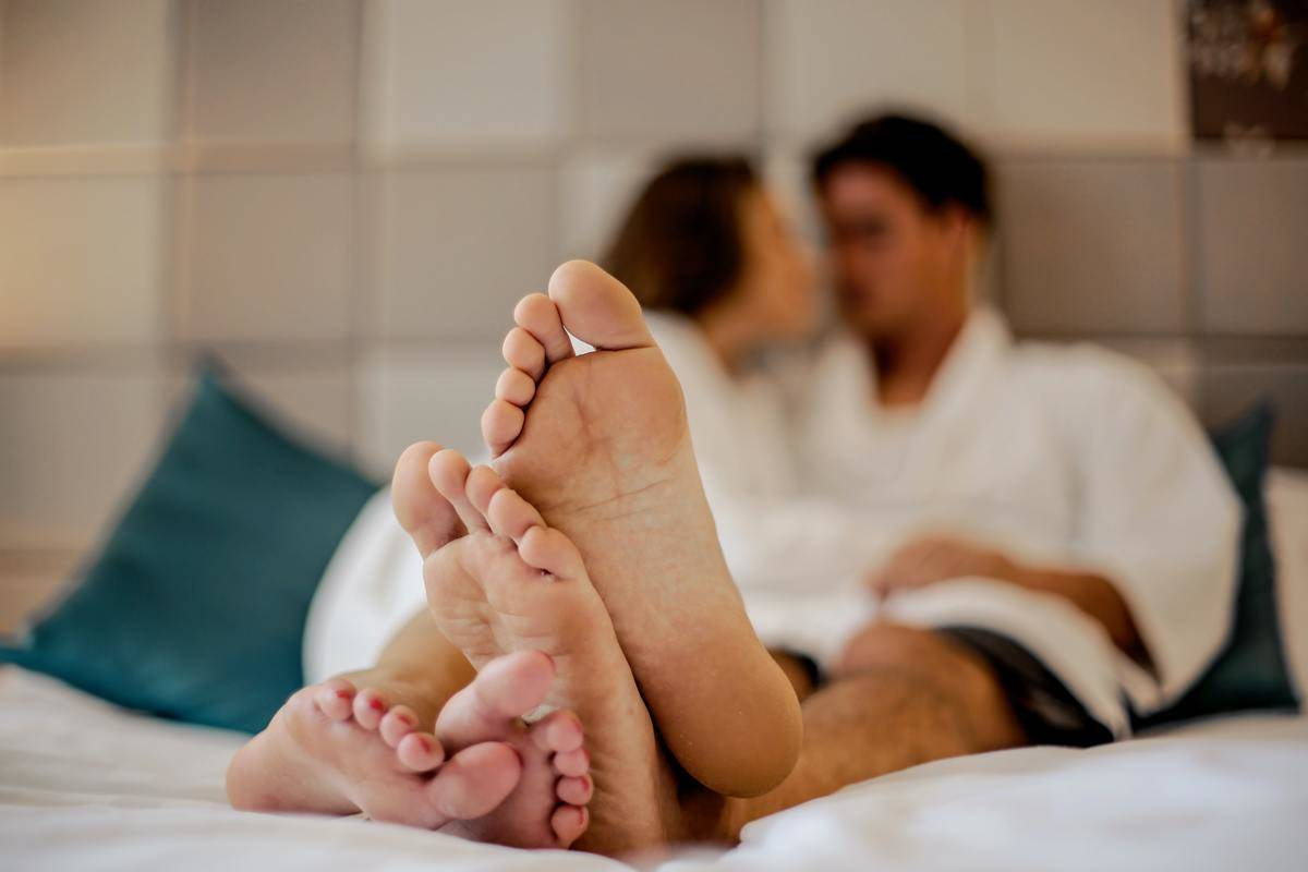 Couple's feet up close in picture taken of them cuddled in bed in hotel room