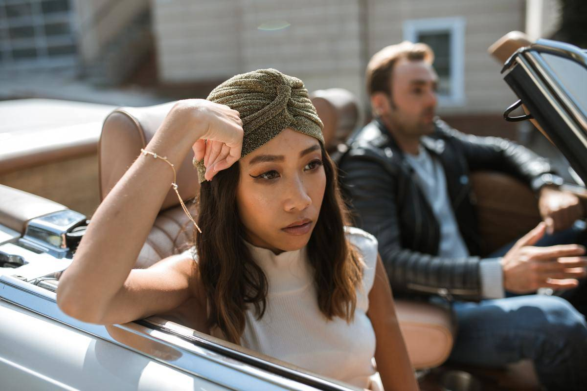 Man and woman sitting in convertible, woman looking into distance