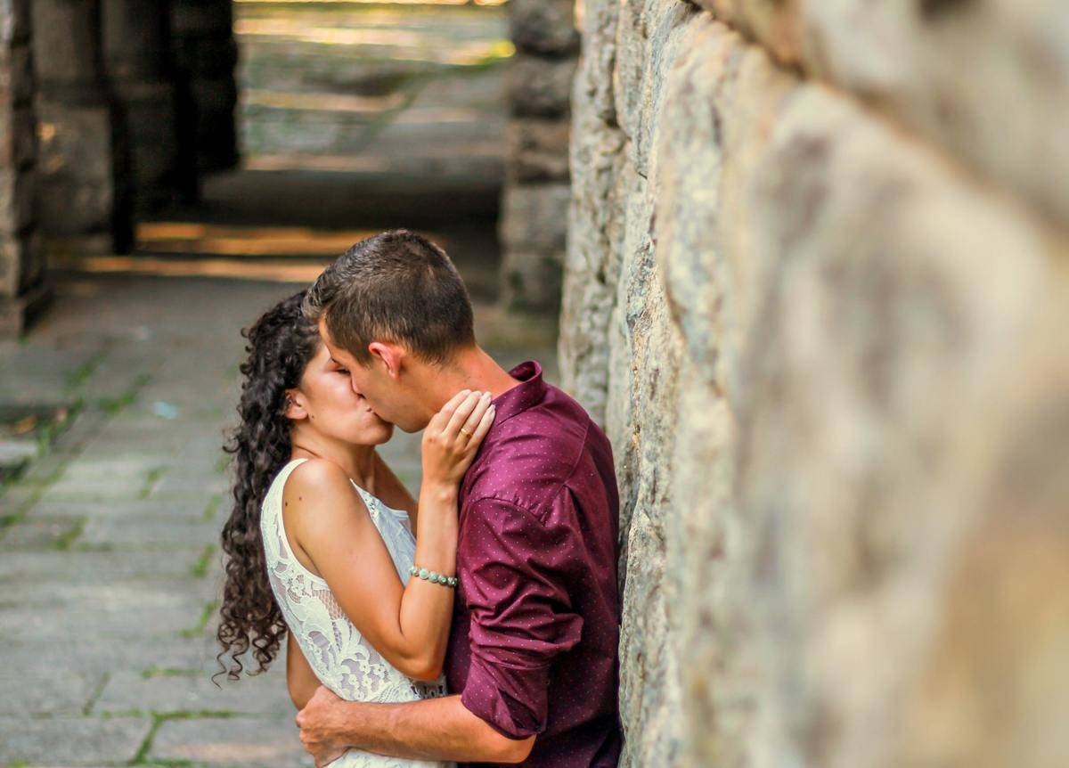 Man and woman kissing outside against stone wall