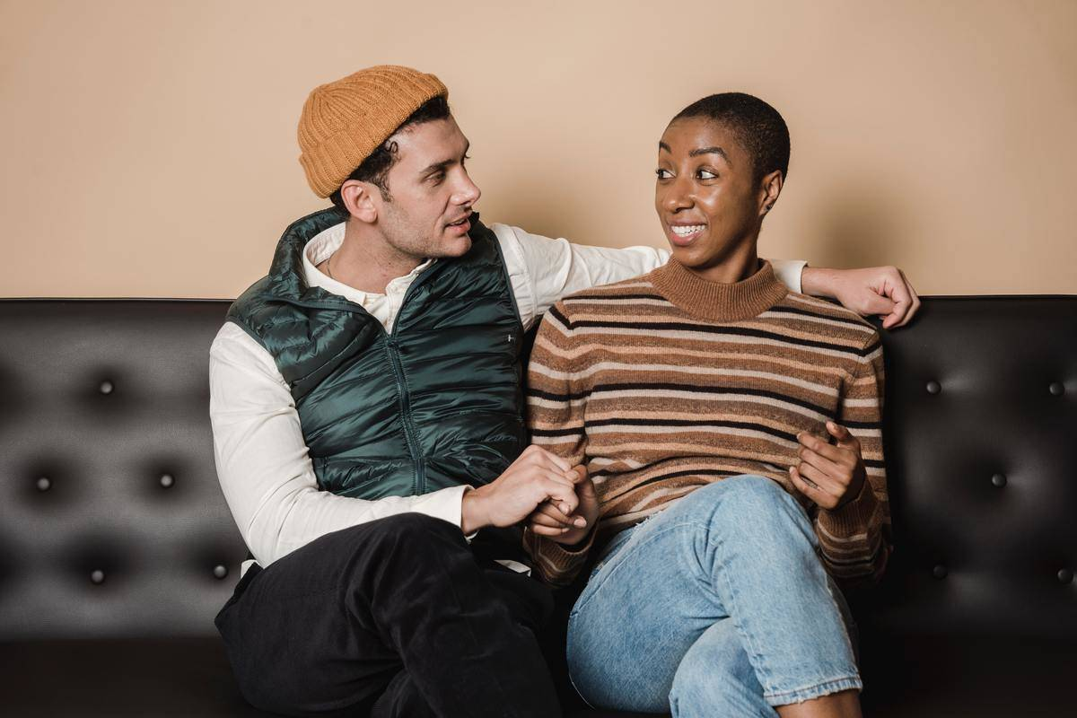 Man and woman sitting together on couch holding hands; woman giving man a confused look