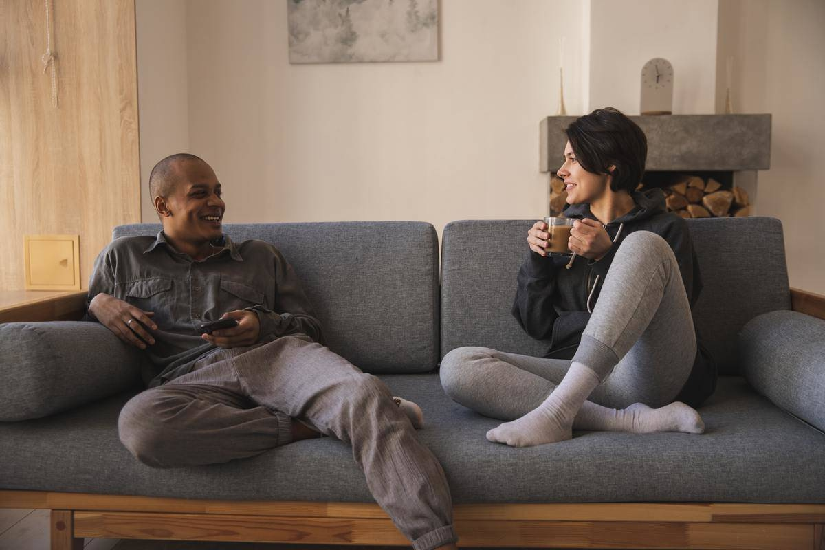Man and woman sit on couch, woman holds mug, man smiling