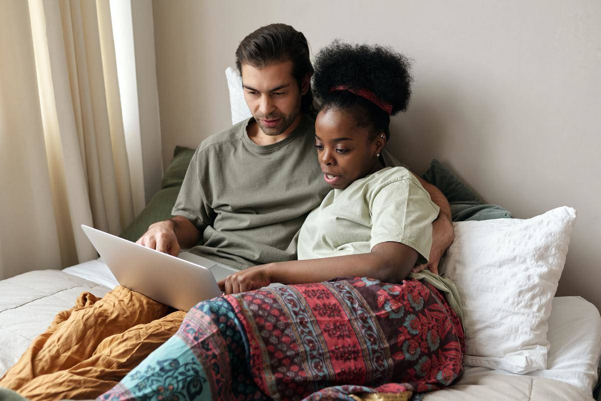 Couple sits on couch looking on laptop