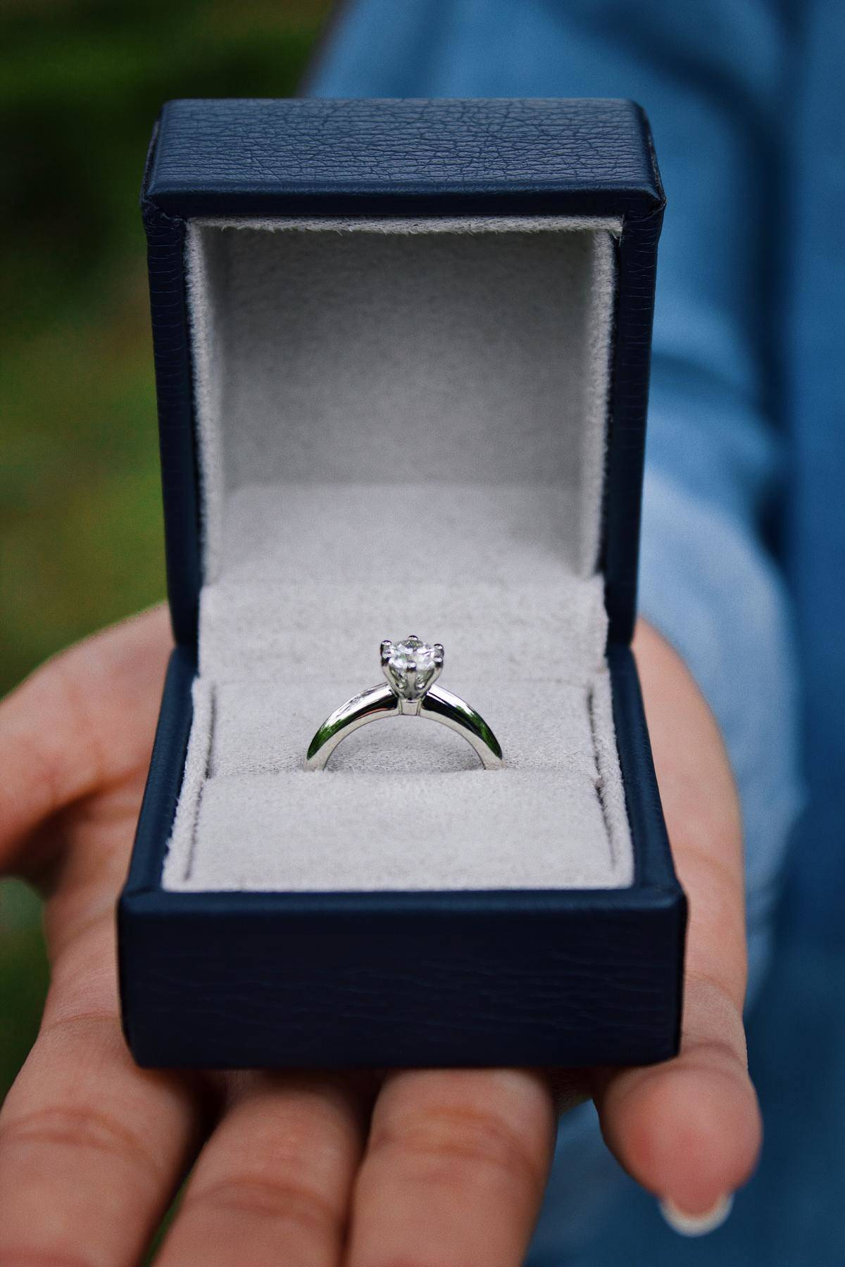 Hand holds out a box that contains a diamond engagement ring