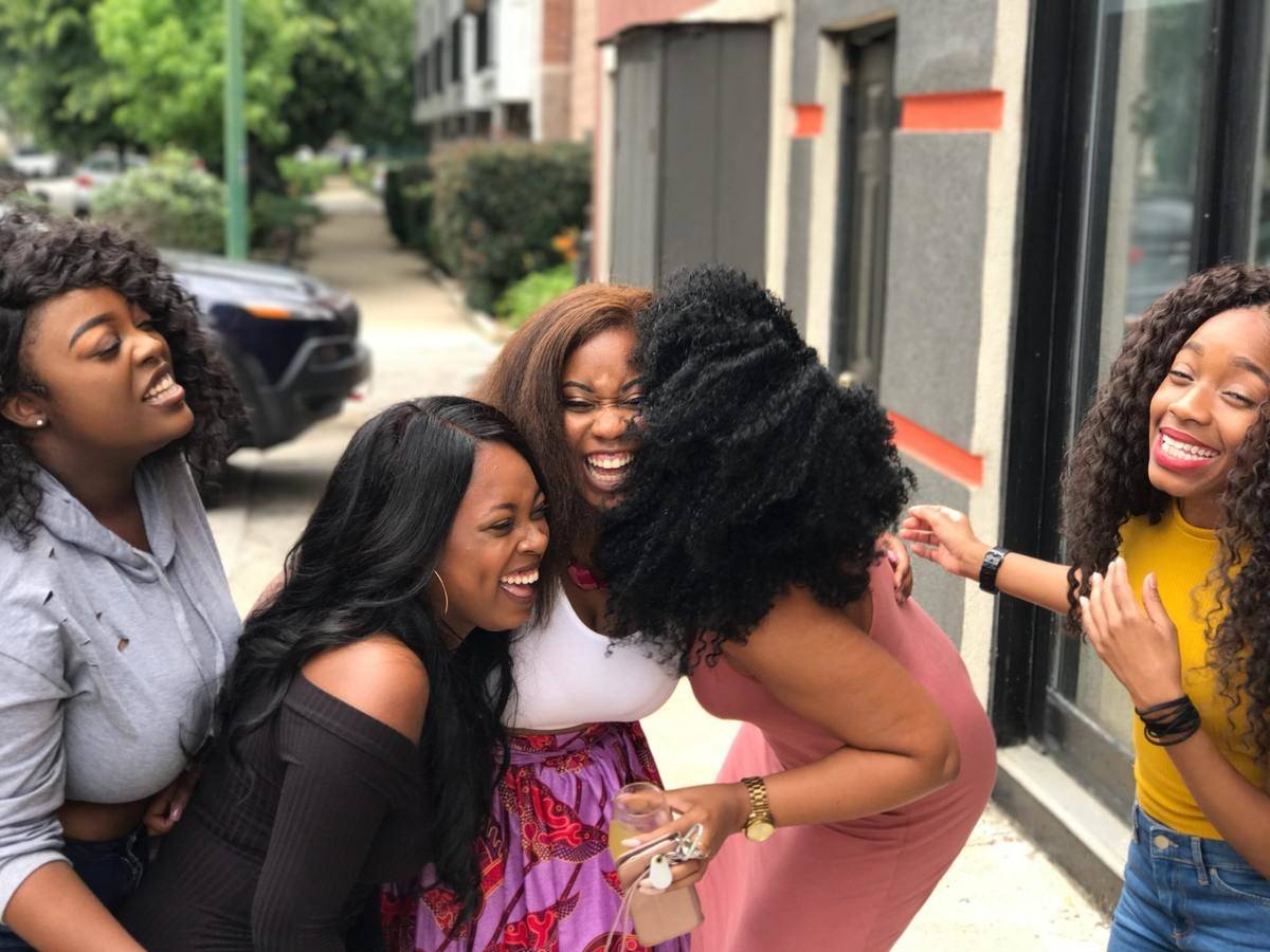 Group of five women laugh and hug on street