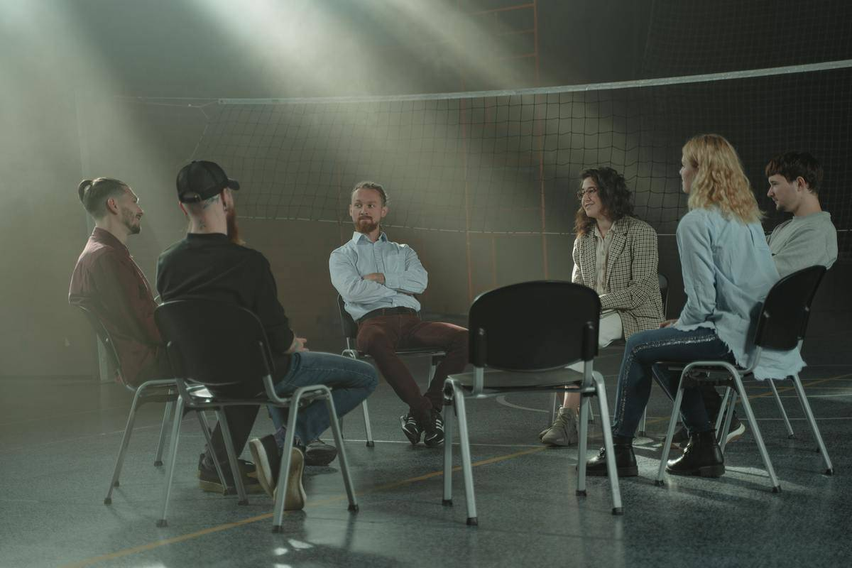 Several people attend a group therapy session in a dark room