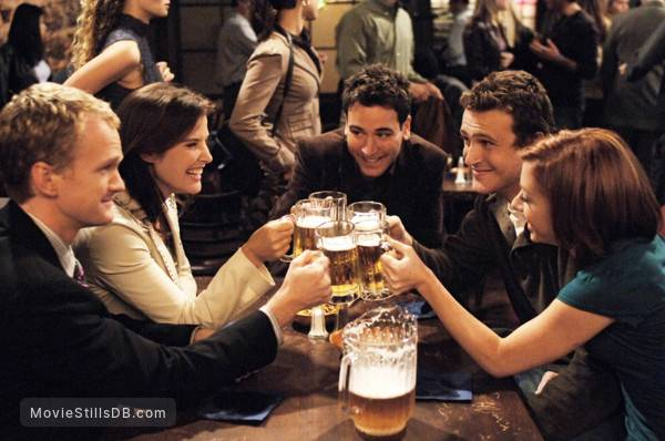 """Cast of """"How I Met Your Mother"""" sitting at a table in a bar cheersing with drinks"""