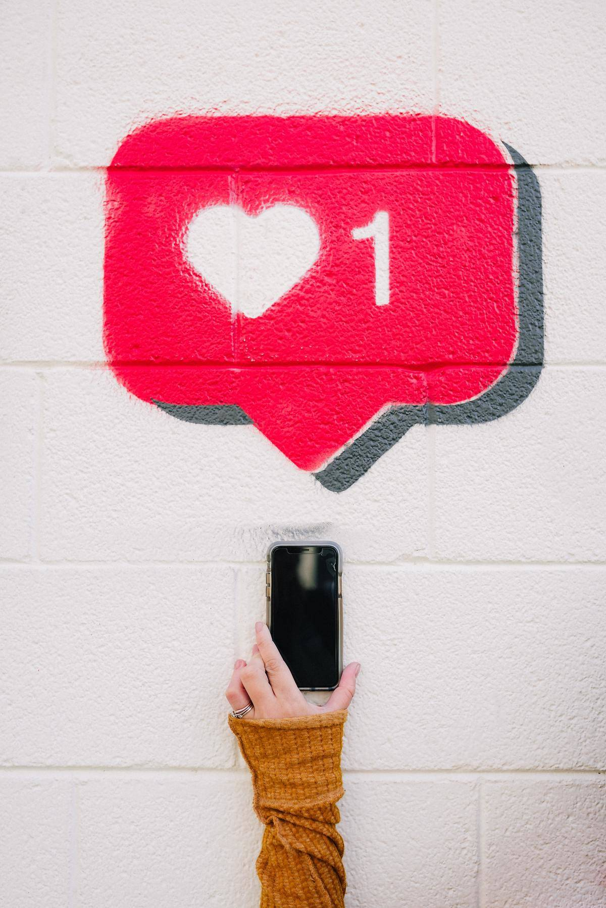 Woman holding a phone with Instagram notification painted on the wall behind her