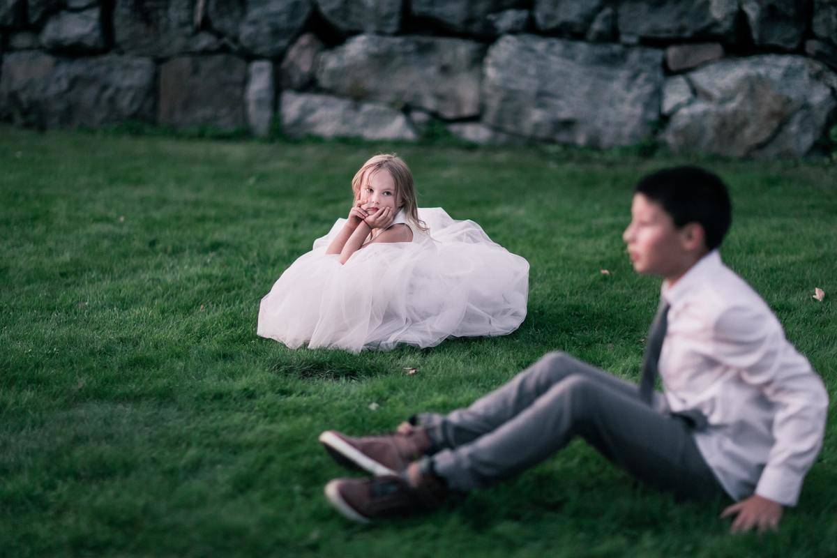 Flower girl and ring bearer sit on the grass