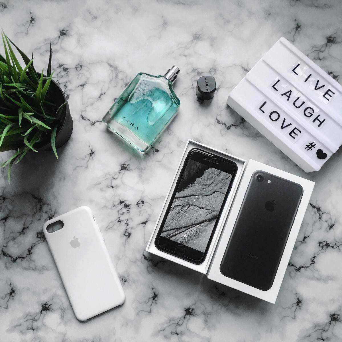A cell phone, bottle of perfume, and light-up sign that says