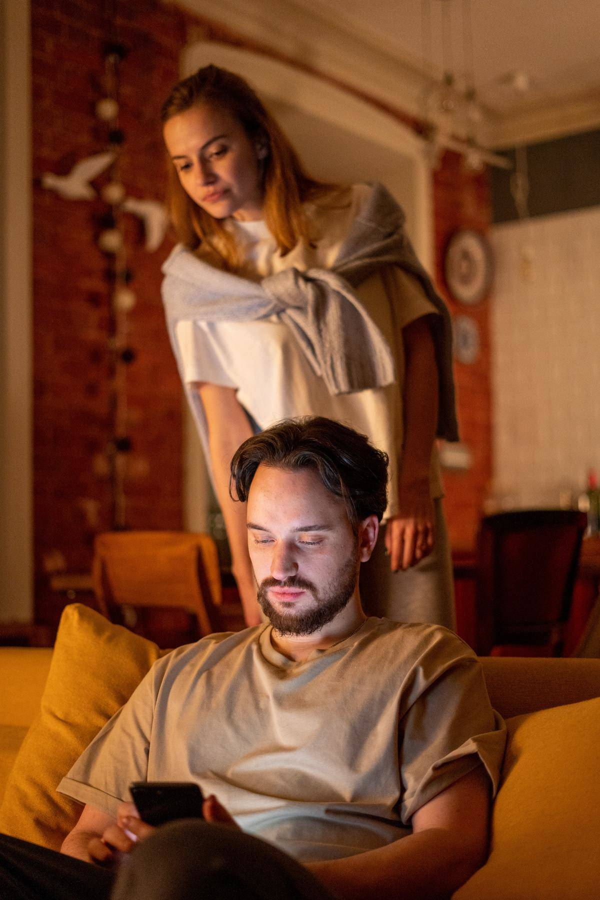 Woman looks over shoulder at man's phone while he sits on couch