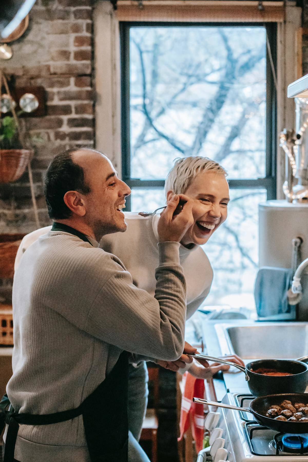 Couple laughs in kitchen, man wears apron and holds spoon for woman to taste