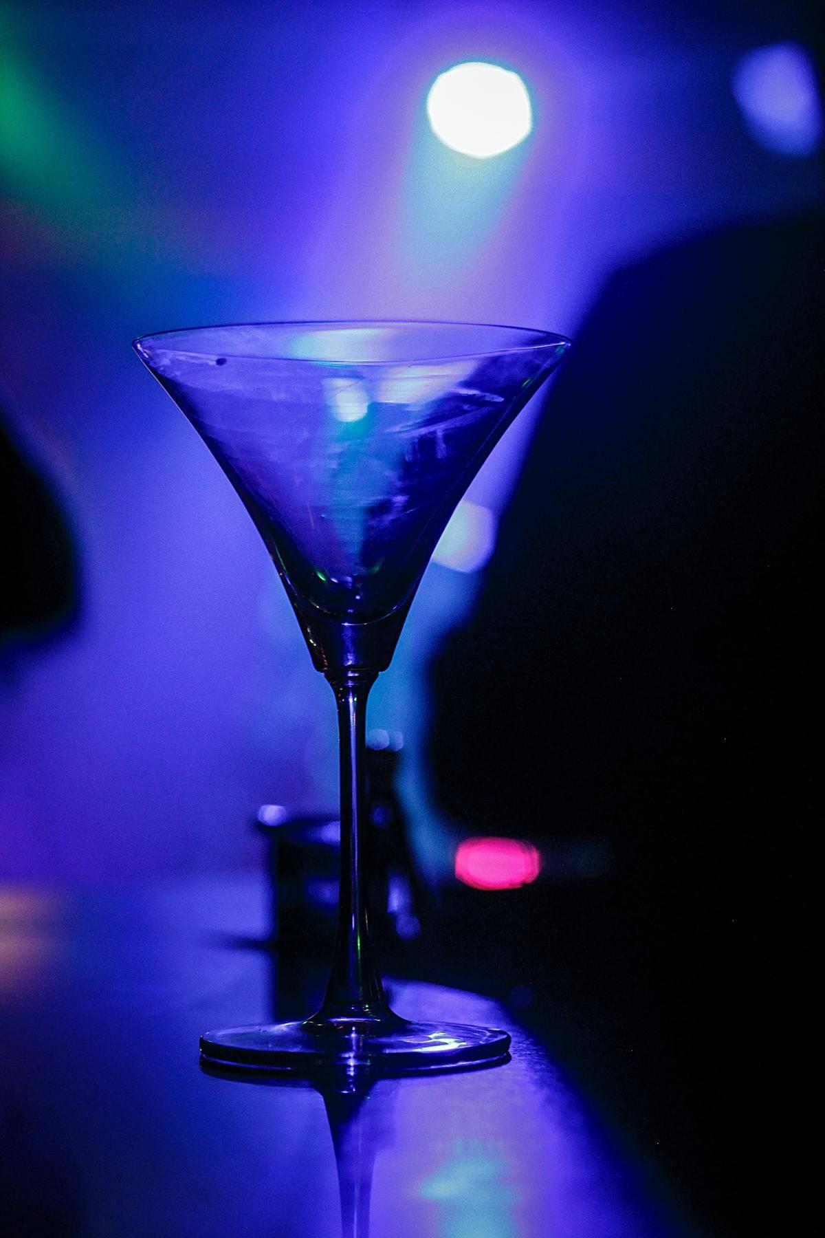 Martini glass on counter amid intense blue lighting