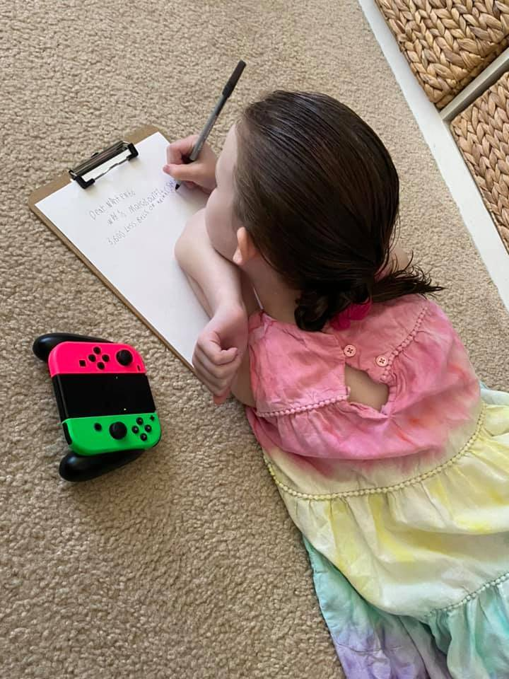 Young girl lying on floor in rainbow dress beside her Nintendo Switch remote as she writes a letter on a clip board