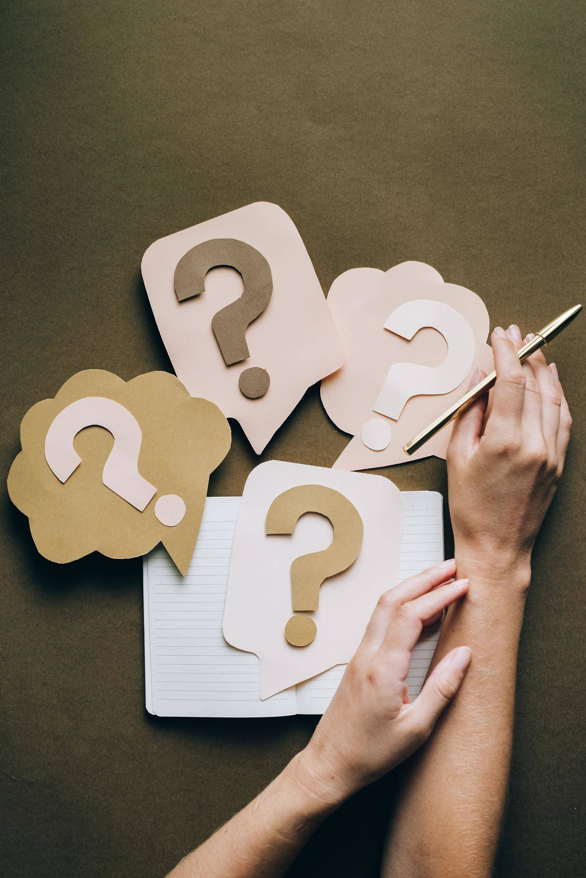 Person holds a pen while there are cutout question marks on the table