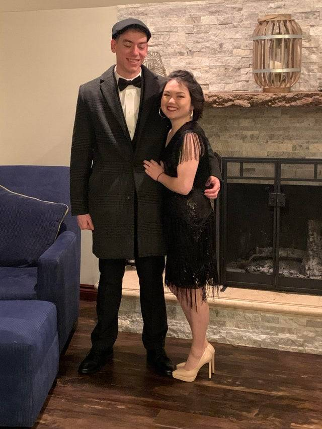A short woman poses with her tall boyfriend while she wears high heels