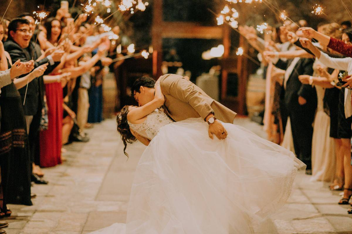 Newlyweds kiss among guests holding sparklers