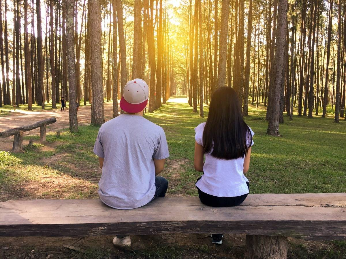 two people sitting in the woods