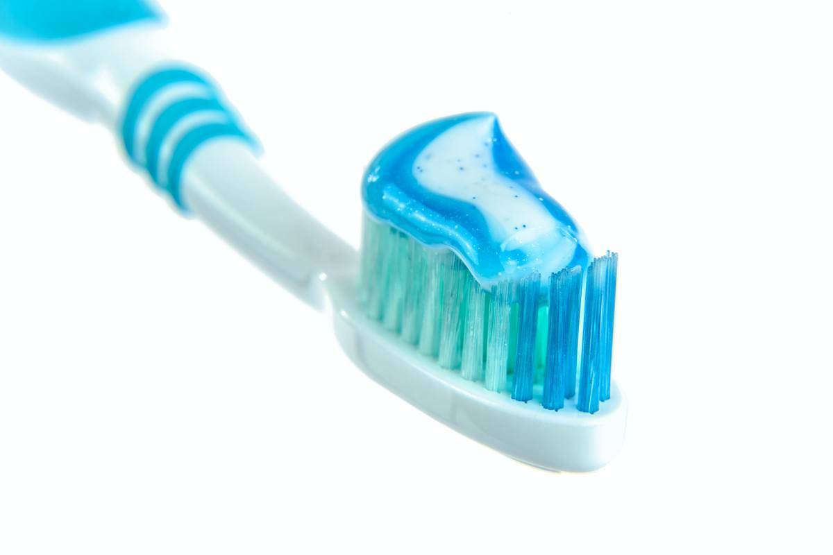 Blue toothbrush with blue toothpaste on it