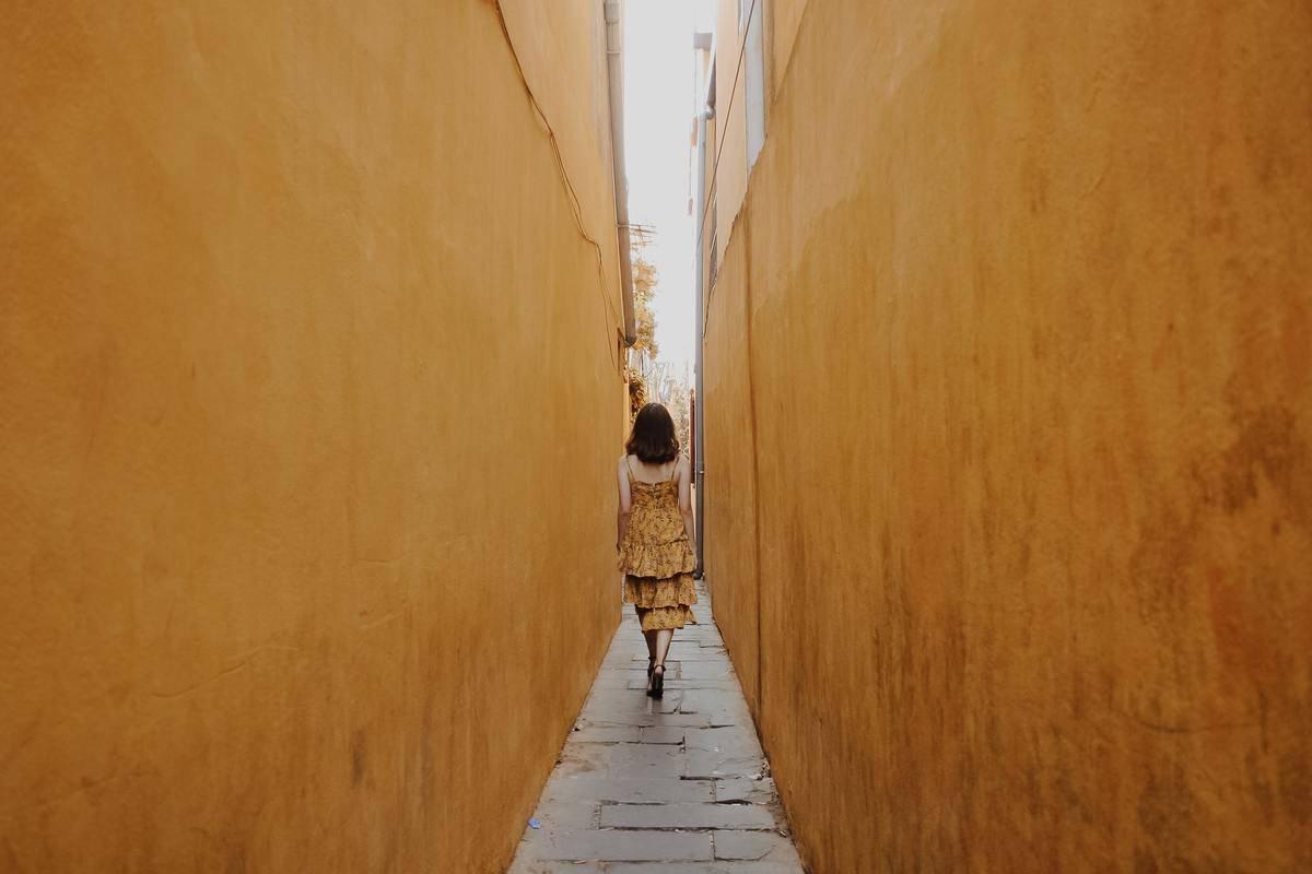 Woman walks alone down thin alley between two orange walls
