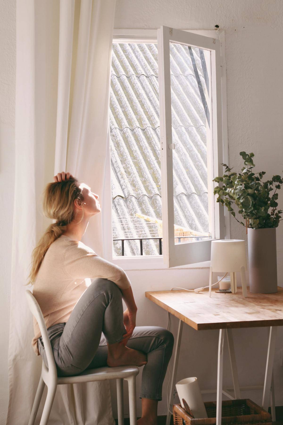 Woman sitting at window and looking outside