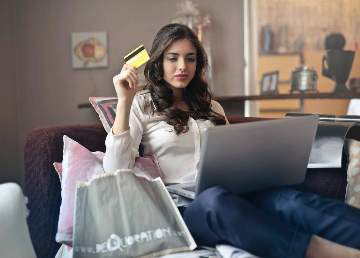 Woman sits on couch on laptop with credit card in hand