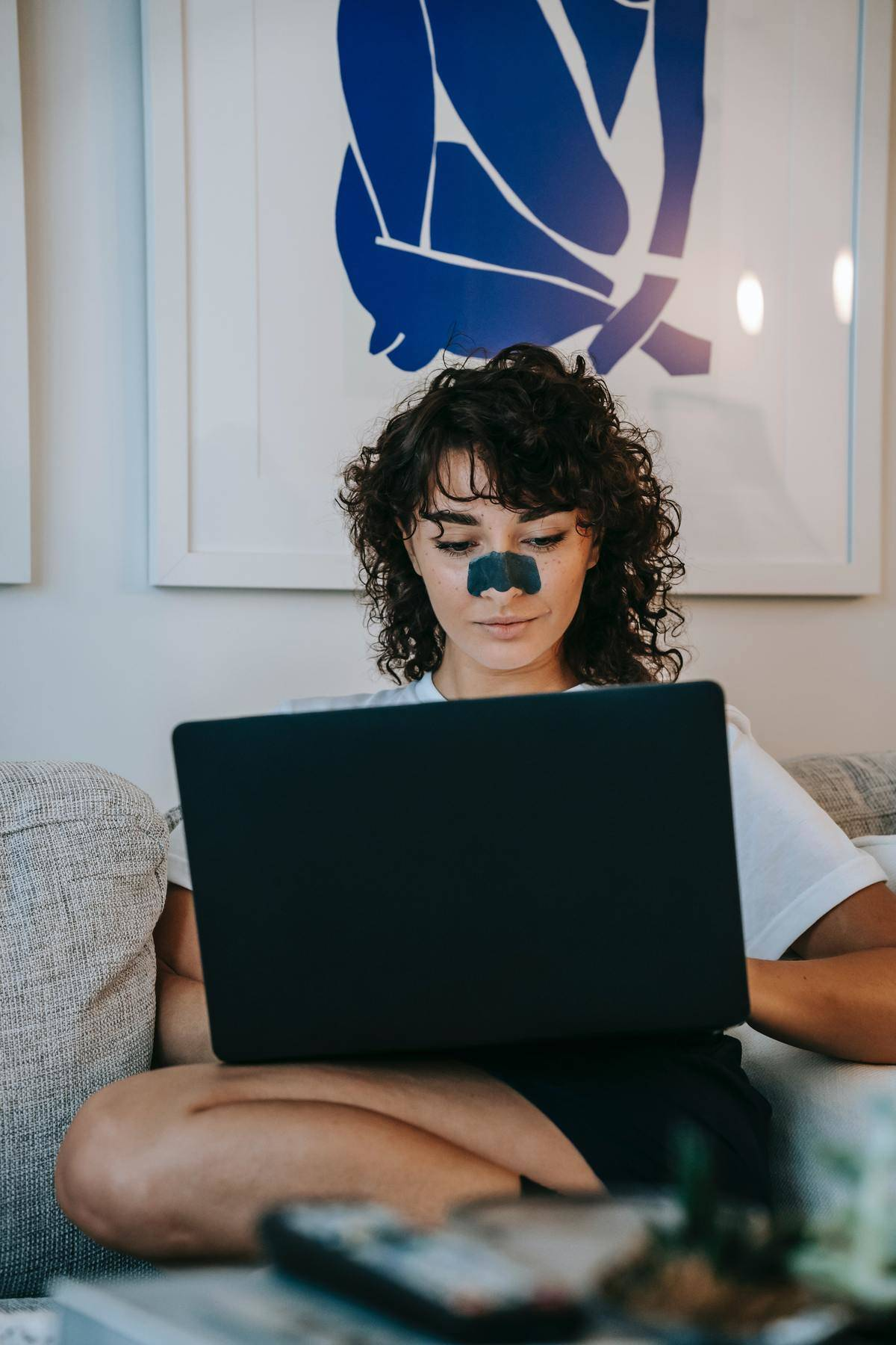 Woman sits looking at laptop with pore strip on her nose