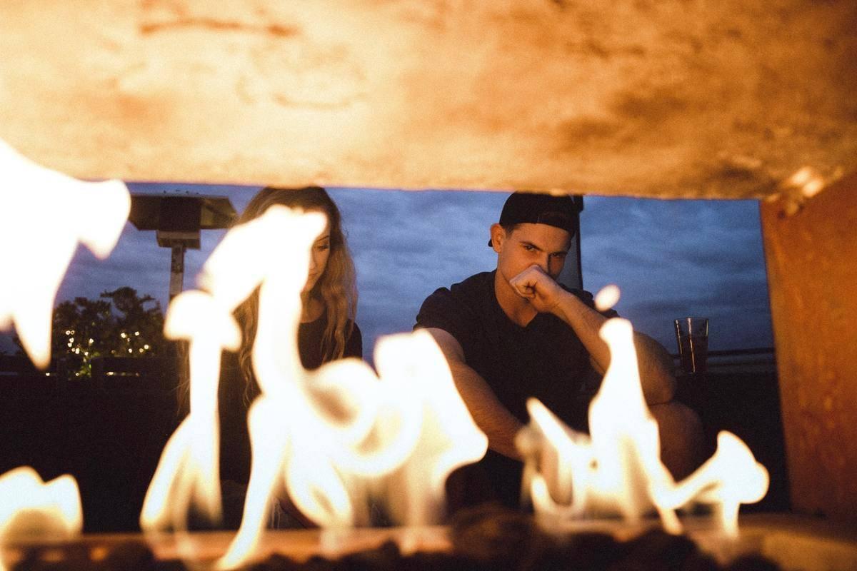 Couple seen behind a fire